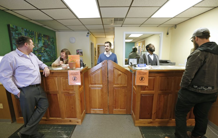Michael Anuszkiewicz, branch manager  at the Buffalo Cooperative Federal Credit Union, center, informs loan manager Brandon Beckinghausen, standing left, that he has an appointment later in the day for a customer requesting a loan.  (Robert Kirkham/Buffalo News)