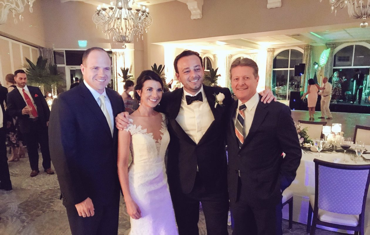 Lauren Rivett and A.J. Baynes, shown here at their wedding earlier this month, previously worked on opposite sides of the political aisle. Rivett was chief of staff to Democratic State Sen. Tim Kennedy, far left, and Baynes held the same post in the office of Republican State Sen. Pat Gallivan, far right. (Photo courtesy Keith Bryan)