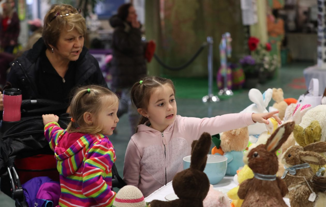 Sisters Sofia, 4, left, and Lydia Barr, 6, look at stuffed bunny rabbits from the Adam's Apples stand in the Broadway Market with their grandmother Fran Nowak of Depew. (Sharon Cantillon/Buffalo News)
