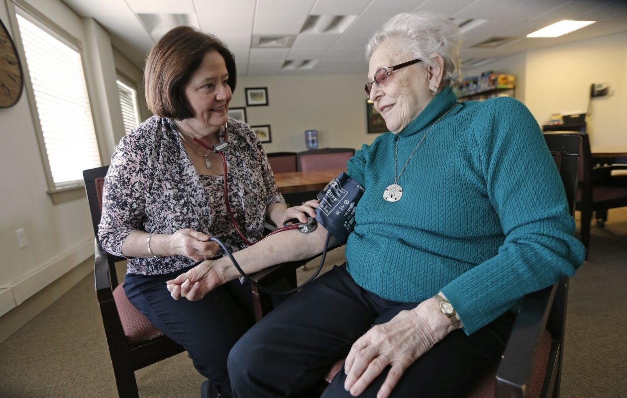 Ellen Pautler, left, a wellness nurse at Fox Run at Orchard Park, takes a blood pressure reading for Lorraine Budzilo, 88, who lives in the independent living section of the continuing care retirement community. Pautler, of Lancaster, used an online shared decision-making tool while considering shoulder surgery. (Robert Kirkham/Buffalo News)