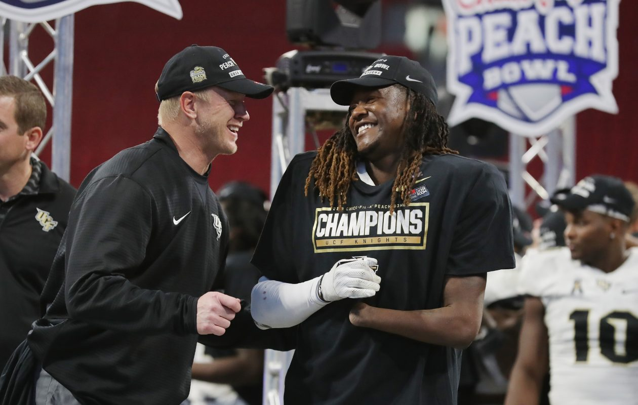 Head coach Scott Frost of the UCF Knights celebrates with Shaquem Griffin (No. 18) after defeating the Auburn Tigers 34-27 to win the Chick-fil-A Peach Bowl on January 1, 2018 at Mercedes-Benz Stadium  in Atlanta, Ga.  (Photo by Streeter Lecka/Getty Images)