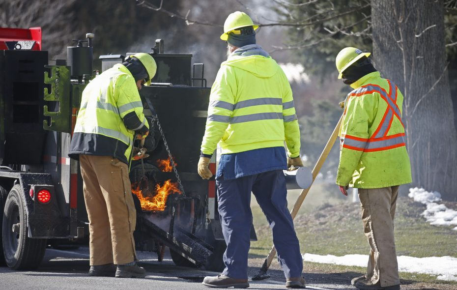 A work crew from the Niagara County Highway Department uses the department's new pothole patcher on Beebe Road near Ridge Road in Newfane. The patcher dispenses a heated material that flows into potholes, filling and sealing them. (Robert Kirkham/Buffalo News)