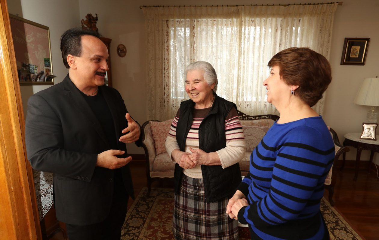 Peter LoJacono, left, president of the Federation of Italian American Societies, speaks with North Buffalo sisters Gaetana, center, and Carmela Campanella at their home. (Sharon Cantillon/Buffalo News)