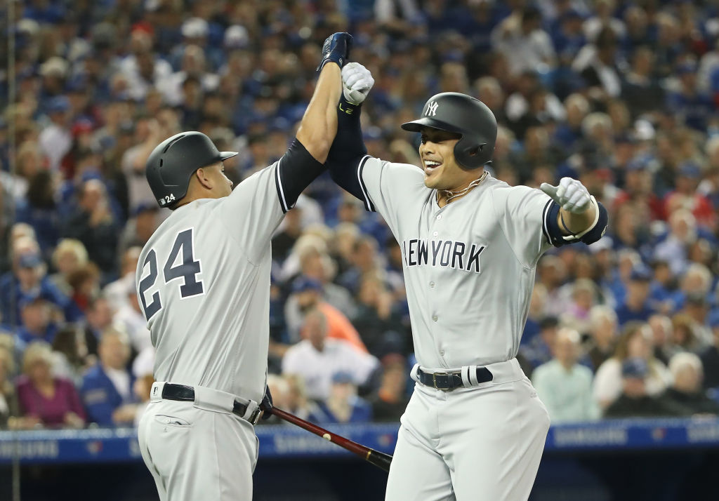 Giancarlo Stanton is greeted at home plate by Gary Sanchez (24) after belting a two-run homer in his first at-bat as a Yankee Thursday in Toronto (Getty Images).
