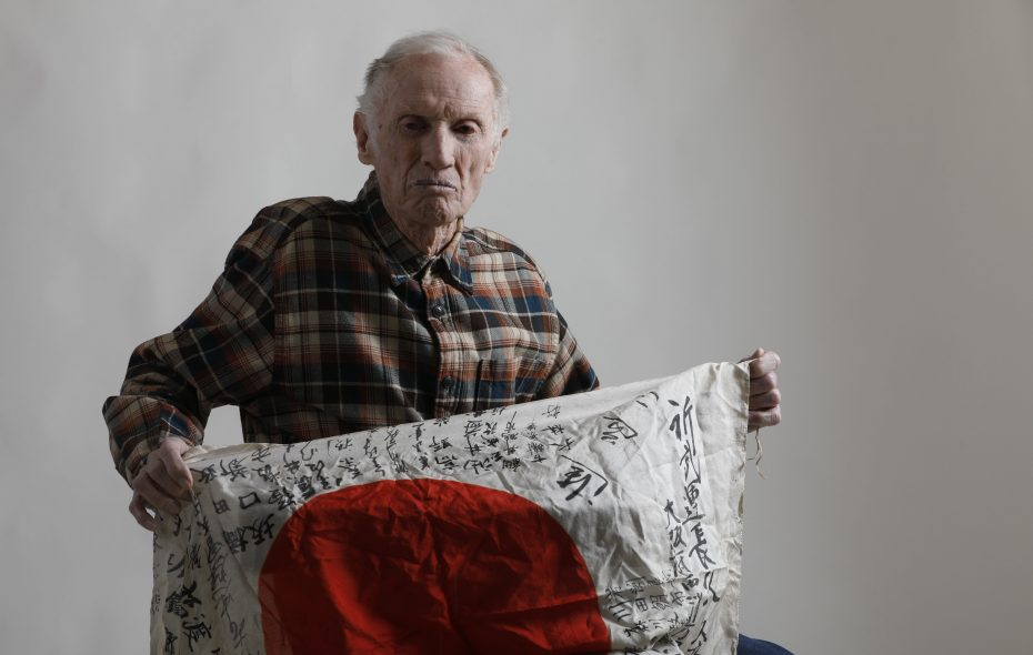 World War II Navy vet Clayton F. Eldridge holds up a Japanese flag he kept as a souvenir from his time shelling enemy forces before the United States' atomic bombs ended the war. (Derek Gee/Buffalo News)