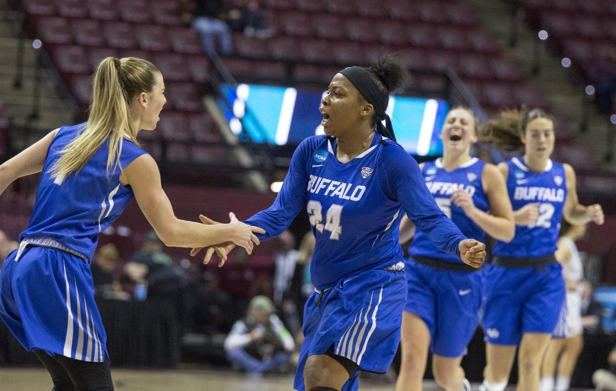 Buffalo guard Cierra Dillard celebrates making a three-point shot with Buffalo guard Stephanie Reid in the first half. (Mark Wallheiser/University at Buffalo)