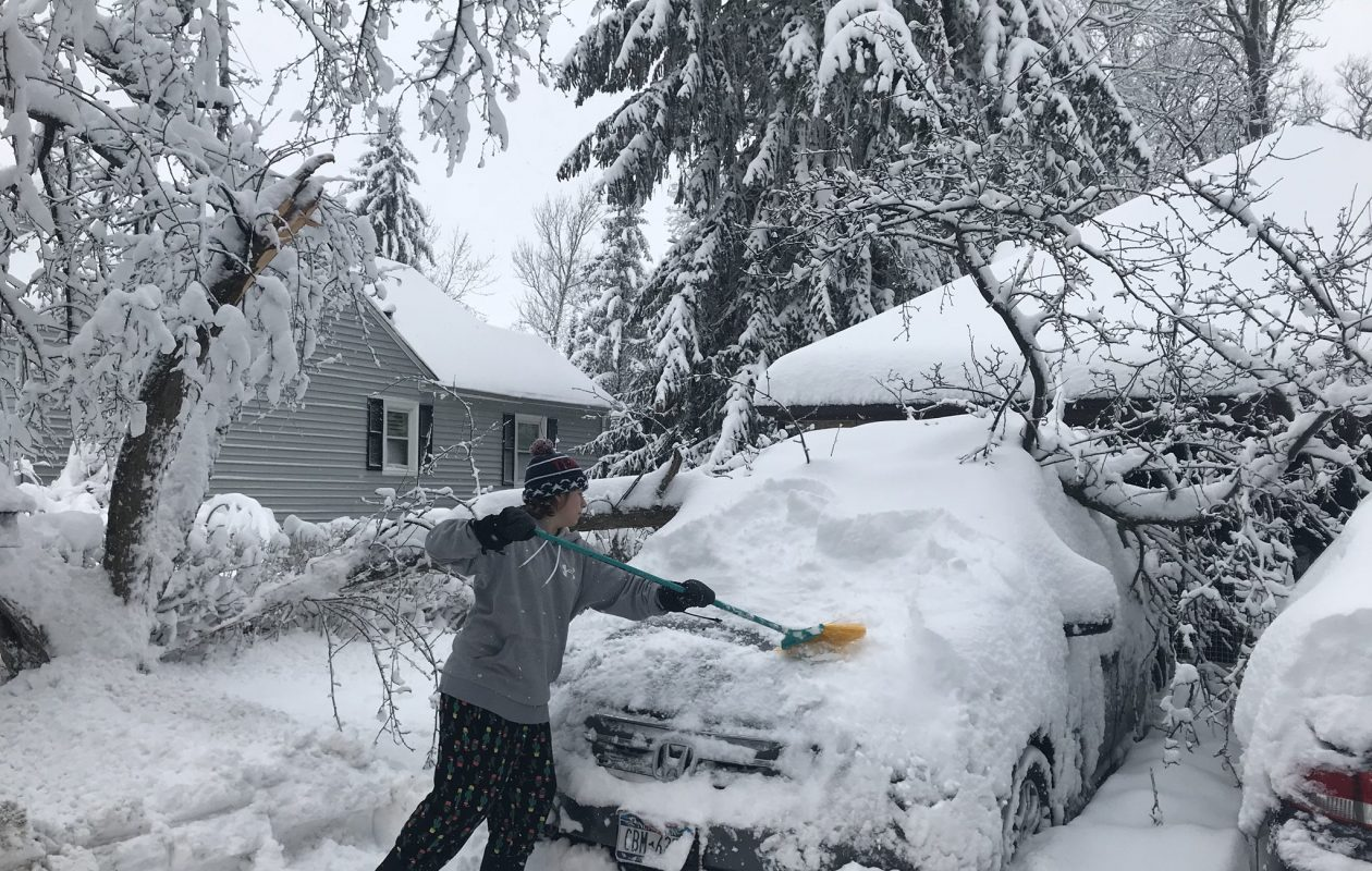 One area resident clears snow off his car, which was struck by a fallen tree branch. (Mark Mulville/Buffalo News)