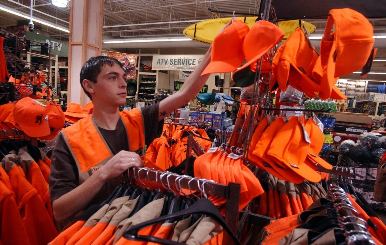 Frank Caseglia, a former sales associate at Gander Mountain in Tonawanda, hangs an orange hat on a rack in 2003. (John Hickey/News file photo)