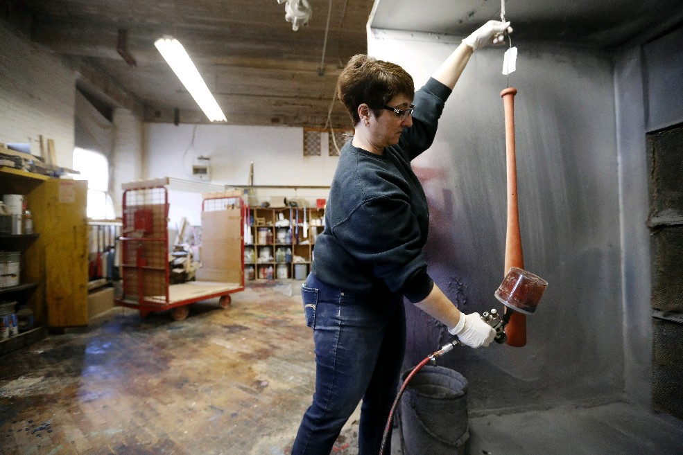 Grace Wheeler applies a finishing coat to a baseball bat at Superior Bat Co. in Jamestown. (Mark Mulville/Buffalo News)