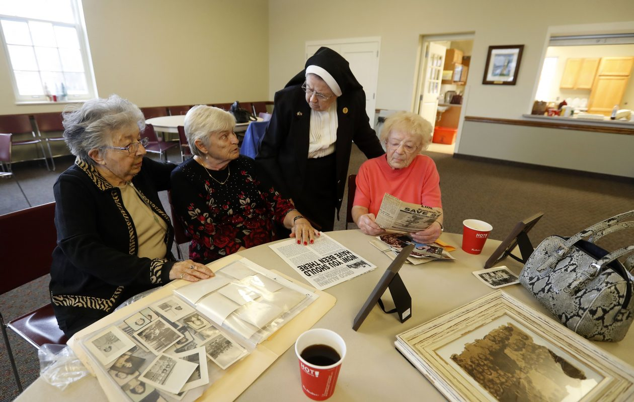 From left to right: Mary Genovese Missana, Myrtle Pickering, Sister Alice Roach and Cleo Cathcart enjoy some coffee and conversation as they look over old pictures and newspaper clippings during a reunion of the German Roman Catholic Orphan Asylum at St. John the Baptist Church in Tonawanda. (Mark Mulville/Buffalo News)