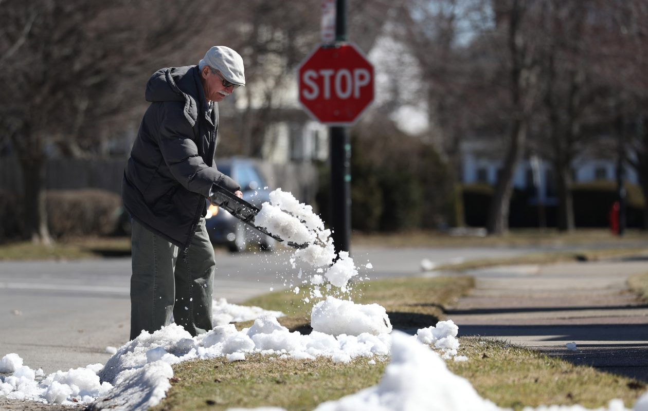 Juan Hernandez spreads out the snow near his driveway on Tacoma Avenue in North Buffalo to get it to melt faster on Monday, March 26, 2018. (Sharon Cantillon/Buffalo News)