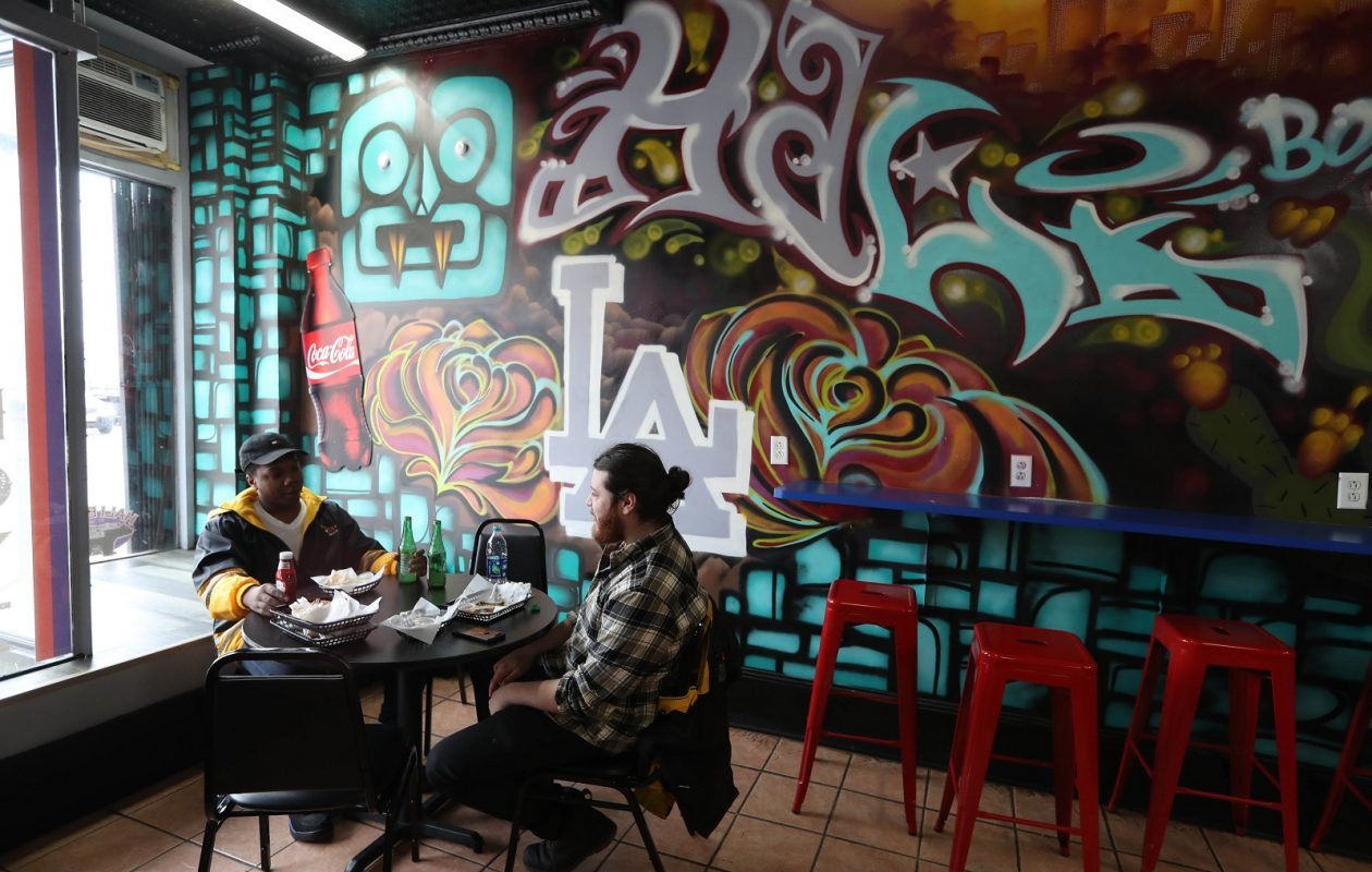 Noah Jones, left, and Drew Montanari of Buffalo stop in to Hali Boyz for lunch. The eat at a table with California-themed graffiti in the background. (Sharon Cantillon/Buffalo News)