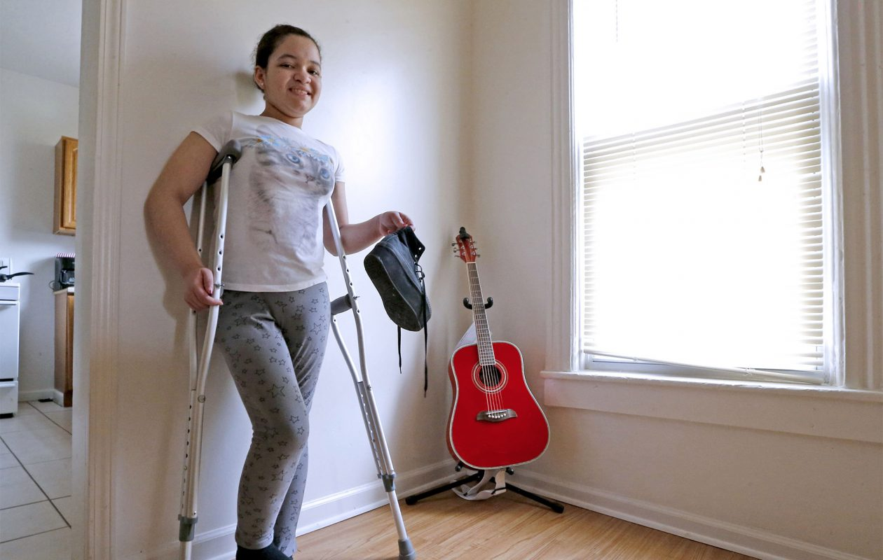 Eva Edwards, 13, holds an orthopedic shoe she no longer needs as she recovers from a life-changing leg surgery at the former Women & Children's Hospital last July. (Robert Kirkham/Buffalo News)