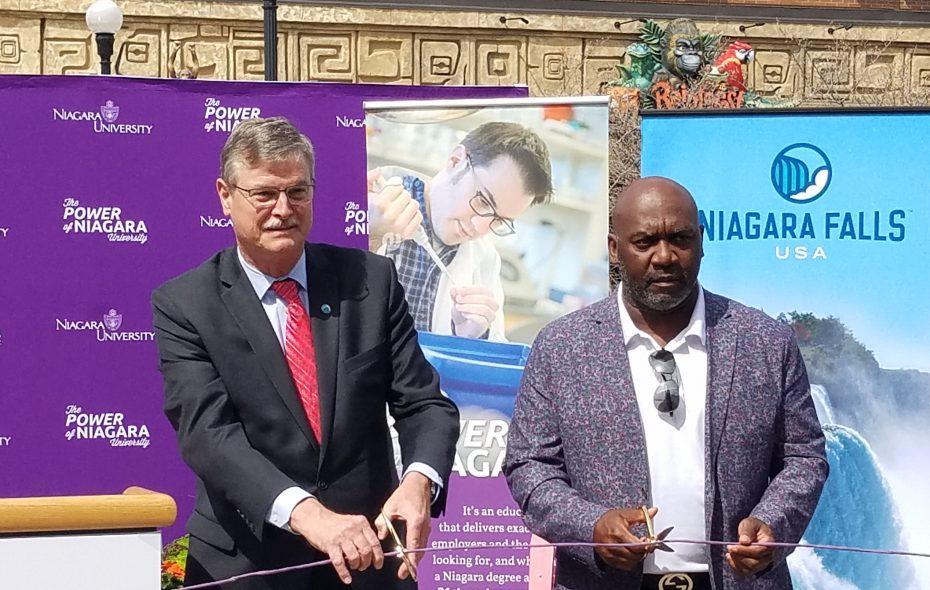 Niagara Falls Mayor Paul A. Dyster and former Buffalo Bill Thurman Thomas cut the Ethernet cable to inaugurate free Wi-Fi service on Old Falls Street in Niagara Falls April 27, 2018. (Thomas J. Prohaska/Buffalo News)