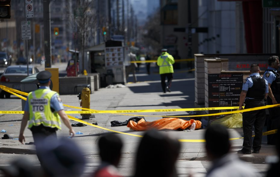 A tarp lays on top of a body on Yonge Street at Finch Avenue after a van plowed into pedestrians on April 23, 2018, in Toronto. (Getty Images)