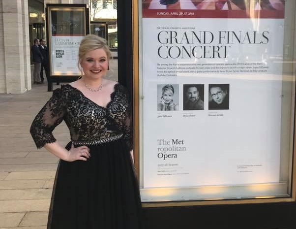 Danielle Beckvermit poses by the poster at Lincoln Center announcing the Grand Finals Concert.