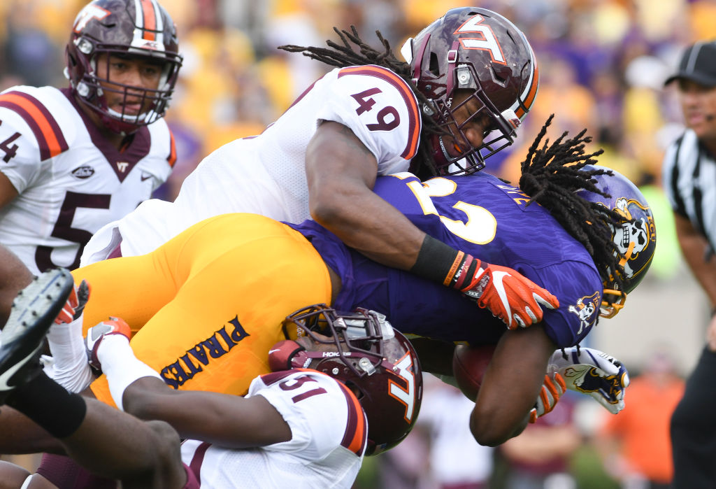 Running back Tyshon Dye #22 of the East Carolina Pirates is tackled by linebacker Tremaine Edmunds #49 and cornerback Brandon Facyson #31 of the Virginia Tech Hokies in the first half at Dowdy-Ficklen Stadium on September 16, 2017 in Greenville, North Carolina. (Photo by Michael Shroyer/Getty Images)
