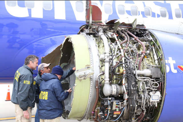 NTSB inspectors examine the damaged engine of the Southwest plane that made an emergency landing in Philadelphia on Tuesday. (NTSB handout photo)