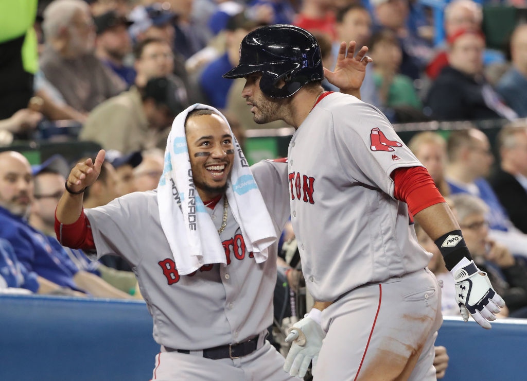 Boston's Mookie Betts, left, congratulates J.D. Martinez after his three-run home run Thursday in Toronto (Getty Images).