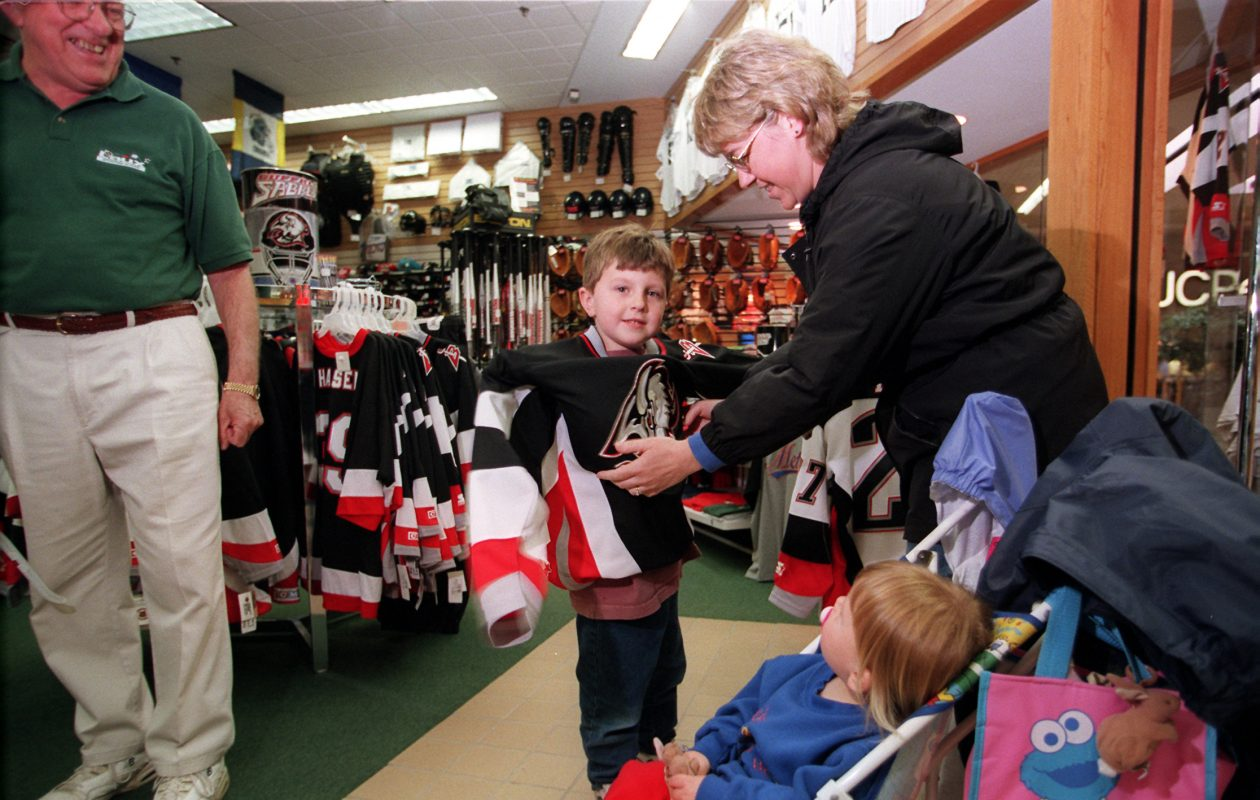 Lisa Lis, helps her son Roger, then 5, try on a Sabres jersey at the Laux Sporting goods store in the McKinley Mall in 1999. (Mark Mulville/Buffalo News)