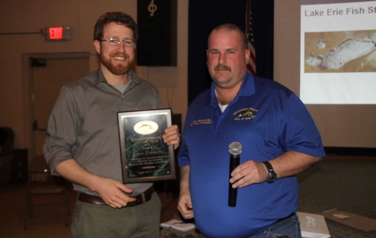 Dr. Jason Robinson with DEC accepts his Conservationist of the Year award from Southtowns Walleye Association's Jim Skoczylas, first vice president with the club.
