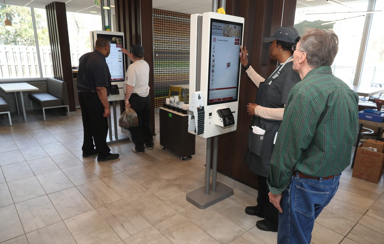 Inez Coleman, guest experience leader at  the McDonald's on Union Road in West Seneca helps Bob Kazmierczak of Buffalo place his order at the new self-service kiosk. (John Hickey/Buffalo News)