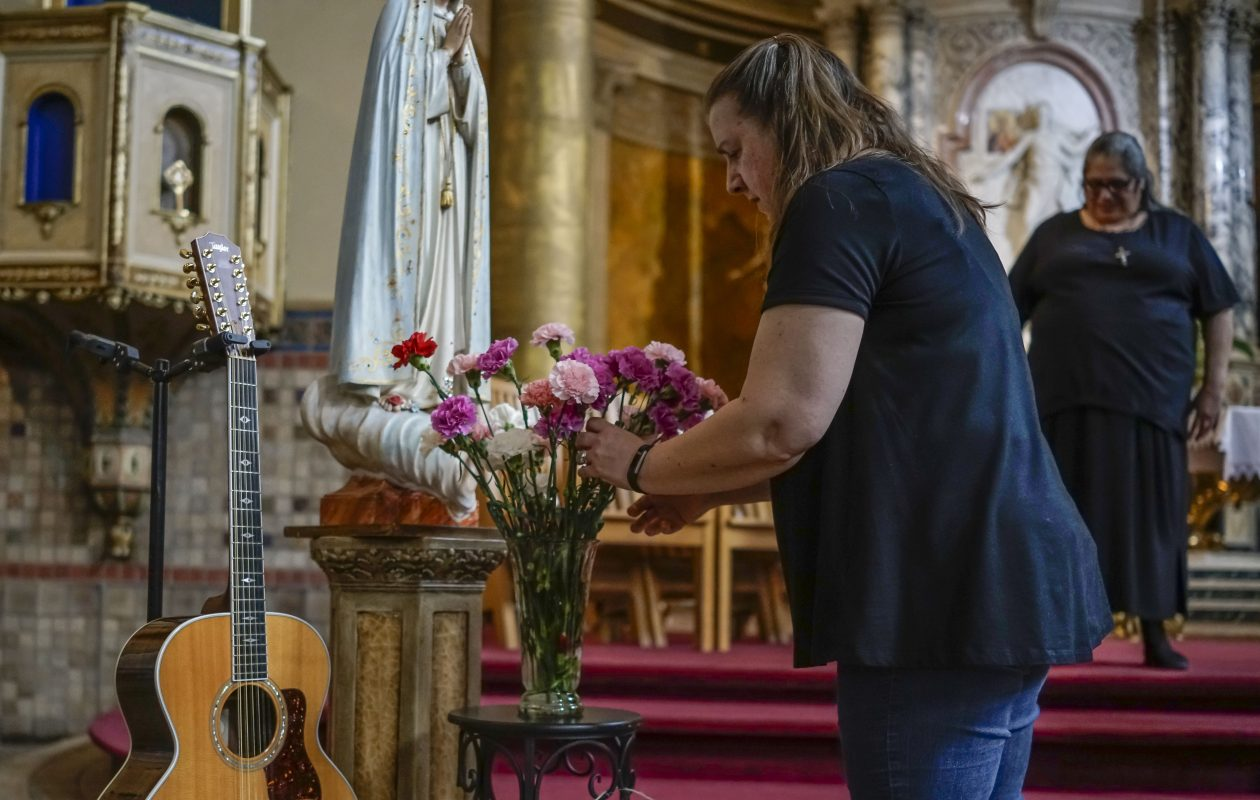 Sue Gilhooley, a missionary and assistant at St. Luke's Mission of Mercy, places flowers at a tribute to co-founder Norman Paolini, who diedlast week after a struggle with Parkinson's disease and brain cancer at the age of 71. Paolini's 12-string guitar is also  part of the display. Looking on is St. Luke's co-founder Amy Betros. (Derek Gee/Buffalo News)