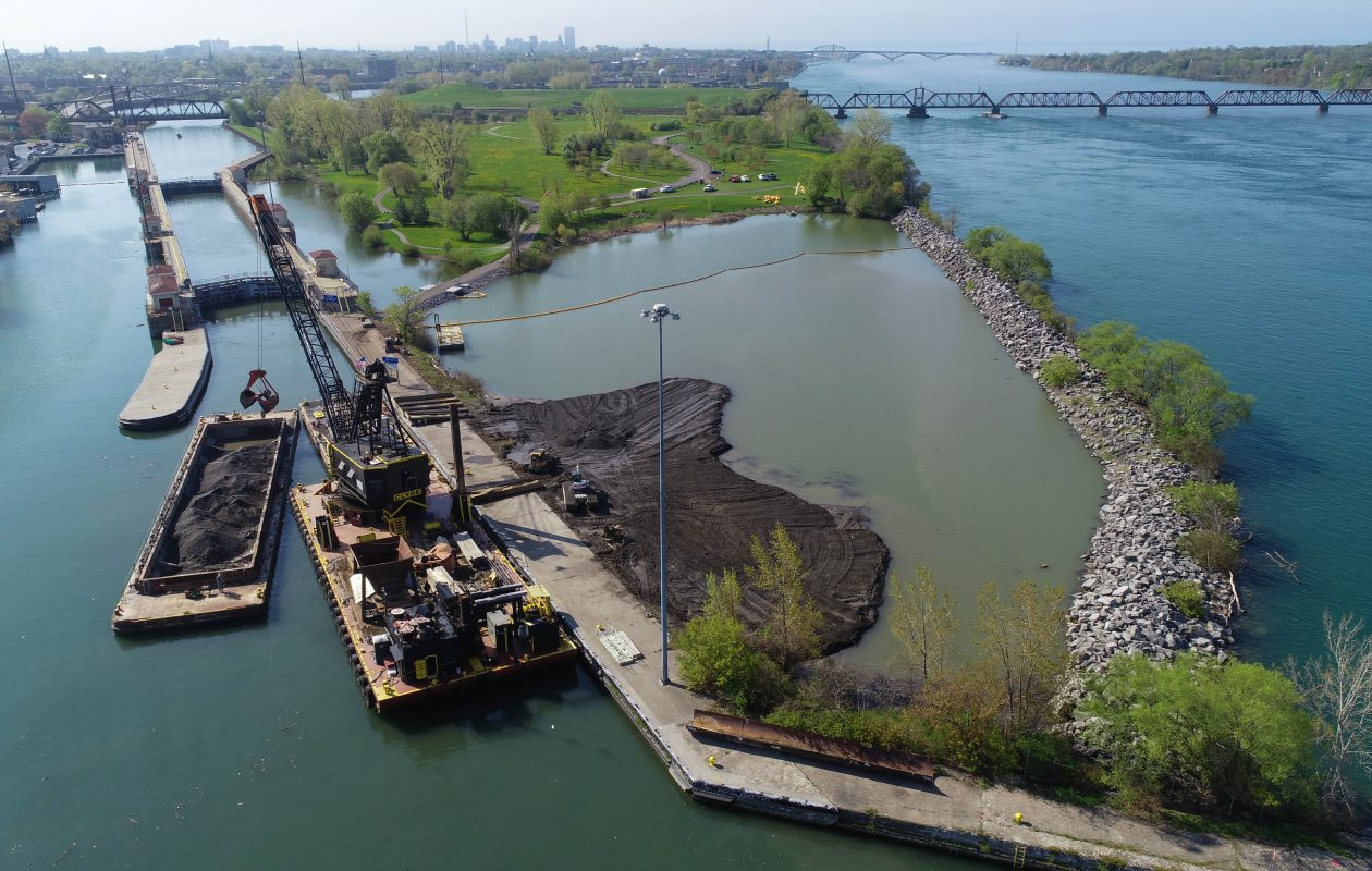 The U.S. Army Corps of Engineers is using clean dredging material from the Buffalo River to create a shallow wetland habitat where a deep pond exists on the northern end of Unity Island, Thursday, May 17, 2018. The crane scoops the fill from the skow, left, into the pond, center, where bulldozers spread out the material into the pond. (Derek Gee/Buffalo News)