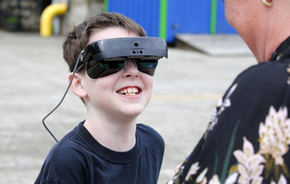 Ronan Christian, who is legally blind, puts on his new electronic seeing device so he can see the animals for the first time at the Buffalo Zoo.  (Mark Mulville/Buffalo News)