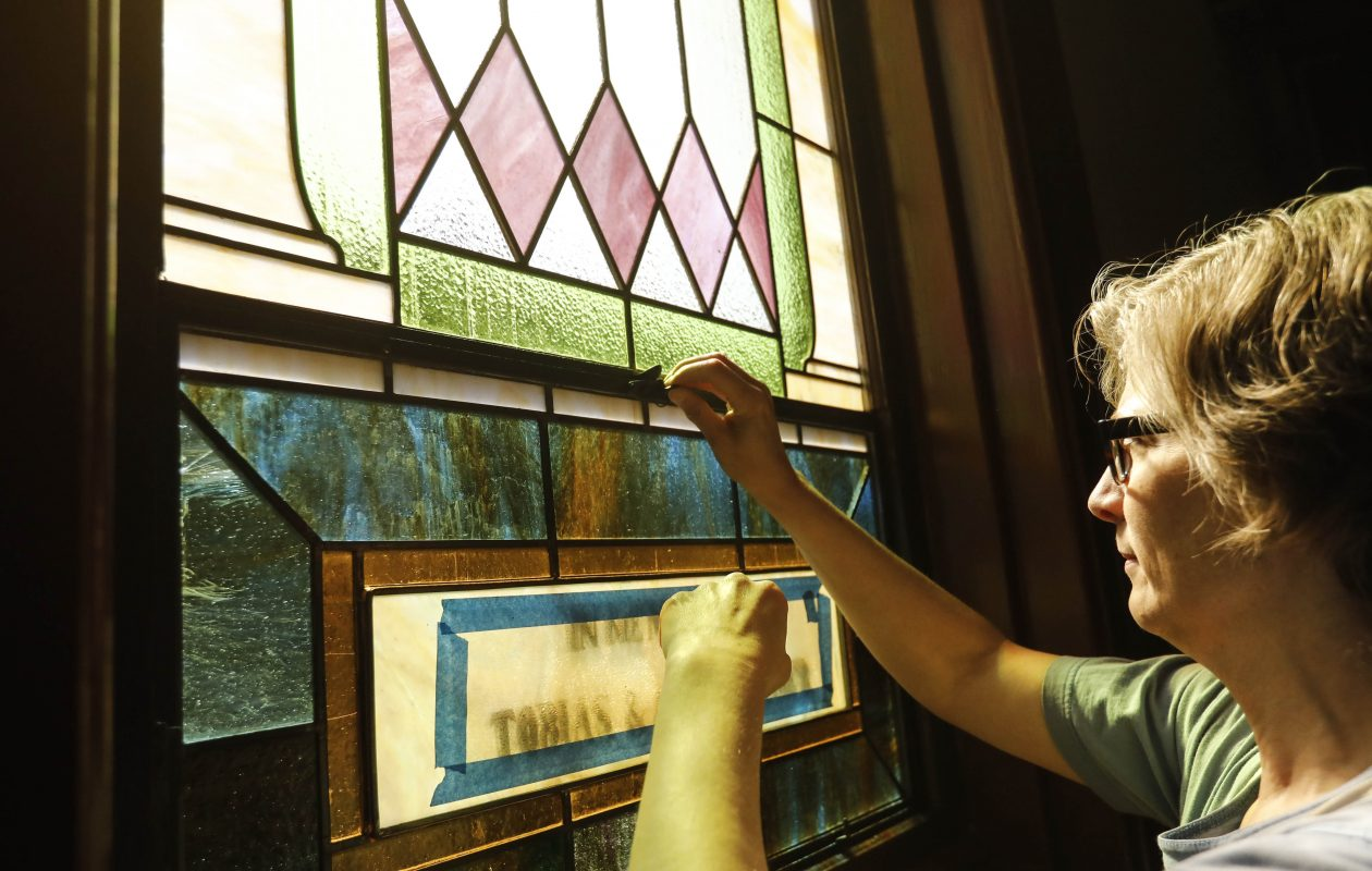 Emily Carlson, owner of Solstice Art Source, installs the memorial window at The Meeting House in Williamsville, Thursday, May 24, 2018. The windows, original to the building when it was built as a church in 1871, were restored by Carlson's team at her Chicago studio. (Derek Gee/Buffalo News)