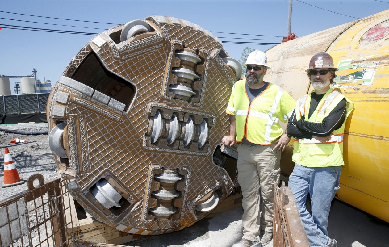Mike Roberts of National Grid, left, and David Keller of Haley & Aldrich, with the machine that dug the tunnel.  (Robert Kirkham/Buffalo News)