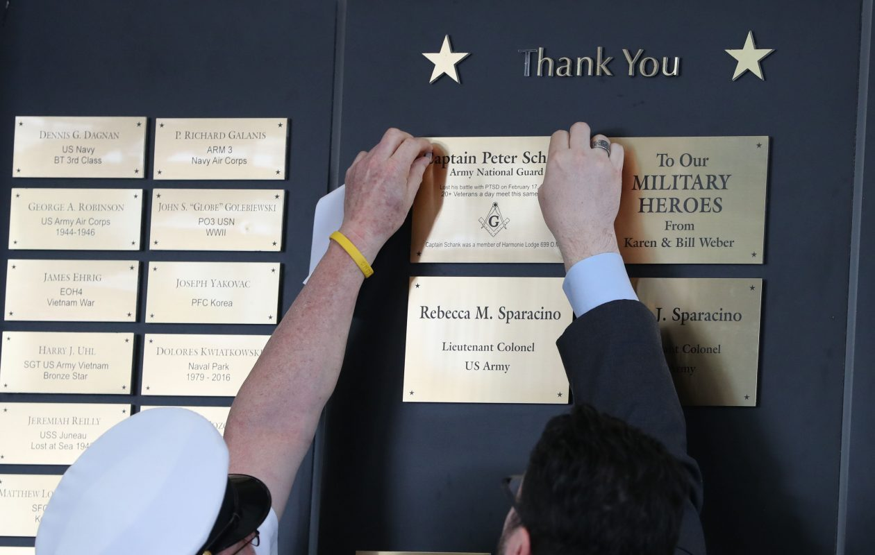 Retired Navy Veteran John Branning, left and Bill Chapin uncover the plaque of Army veteran Peter Schank, who served in Afghanistan, suffered from post-traumatic stress disorder and took his own life last year at the age of 30. (Sharon Cantillon/Buffalo News)