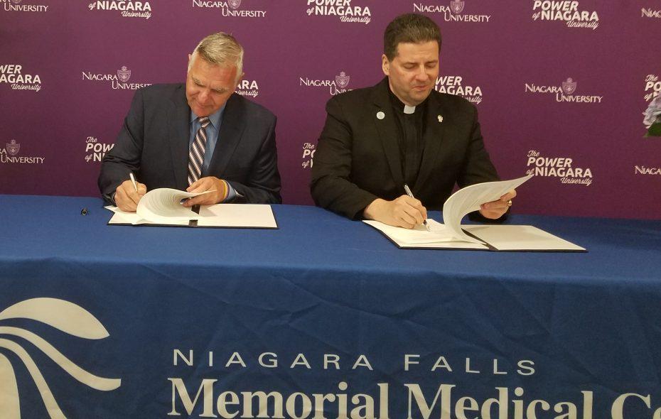 Joseph A. Ruffolo, left, CEO of Niagara Falls Memorial Medical Center, and Rev. James J. Maher, president of Niagara University, sign an agreement on nursing education May 9, 2018. (Thomas J. Prohaska/The Buffalo News)