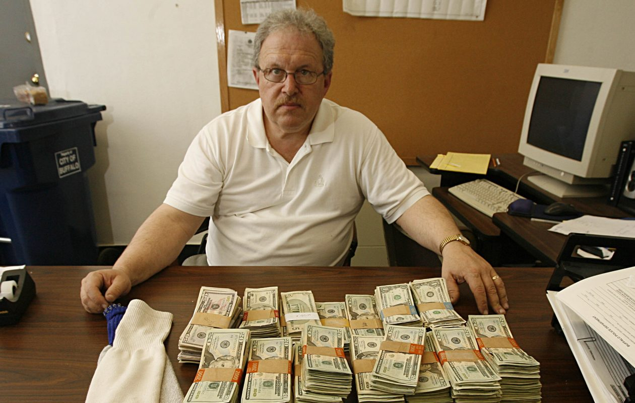 A 2007 photo shows  Buffalo Police Captain Mark Antonio with nearly $100,000 that was  found hidden in two tube socks in a Glenwood Avenue home on Buffalo's East Side. (News staff photo)