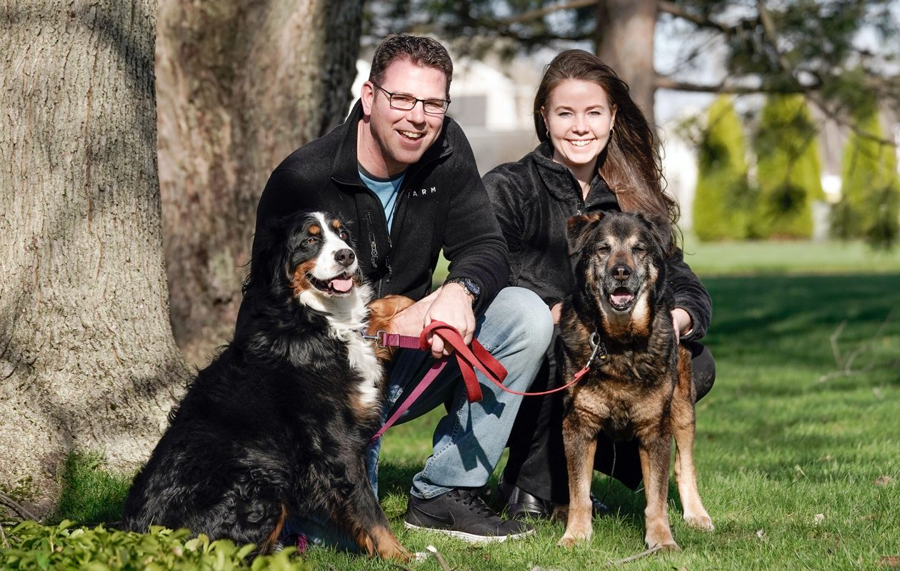 """Writer/comedian Greg Bauch, pictured with wife, Tracy, reflects on being a dog dad to Meg, left, a Bernese Mountain dog and Buck, right, a mix who Bauch describes as """"shepherd, lab, dark dog and my favorite thing on earth."""" (Dave Jarosz)"""