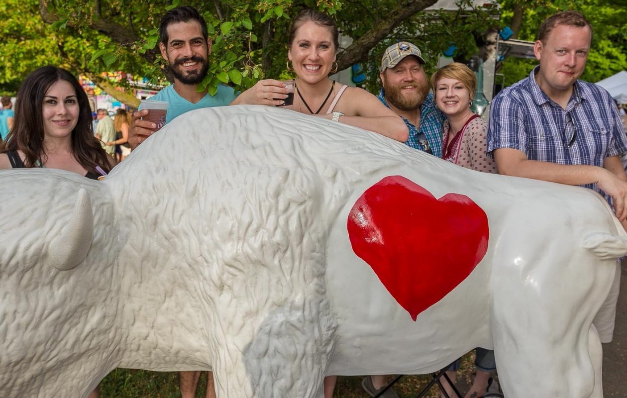 Smiling faces behind a buffalo at BuffaLoveFest, 2016. The annual event returns May 18. (Don Nieman/Special to The News)