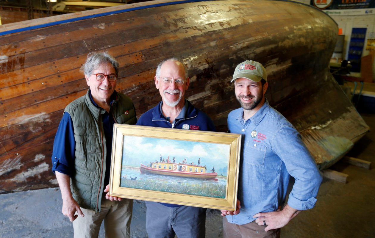 John Montague, left, Roger Allen, center, and Brian Trzeciak hold a painting of a canal boat, similar to the one they are hoping to build for the bicentennial of the Erie Canal at the Buffalo Maritime Center in Buffalo Tuesday, May 8, 2018.   (Mark Mulville/Buffalo News)