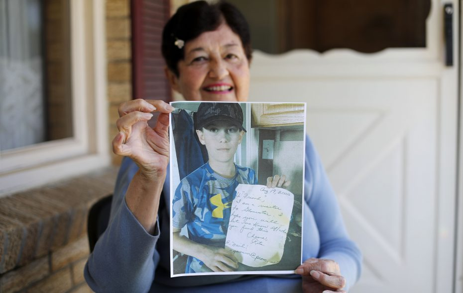 Rita Ganim of West Seneca holds a picture of Dallas Goreham of Nova Scotia, who is holding a message that Ganim tucked inside a plastic bottle and tossed in the ocean on August 19, 2000. Goreham recovered the bottle nearly 18 years later. (Mark Mulville/Buffalo News)