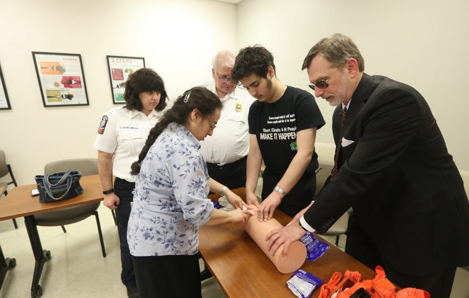 """""""Stop the Bleed"""" is a campaign designed to teach people how to save lives. Here From left, Tracy Chalmers, program manager for Public Health Emergency Preparedness of the Erie County Medical Services, is joined by Gina Kleinmartin; Greg Gill, deputy commissioner of Erie County Emergency Medical Services; Galvan Kleinmartin; and CJ Urlaub, president and CEO of Mercy Hospital. The group was practicing with a """"trauma trainer limb"""" at Mercy Comprehensive Care Center, 397 Louisiana St. (John Hickey/Buffalo News)"""
