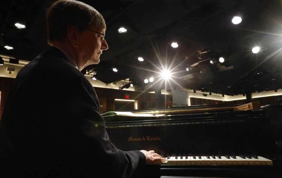 Thomas Witakowski, a musician, professor and conductor of the Buffalo State Philharmonia Orchestra, sits at the piano in the recital hall in Rockwell Hall. (Derek Gee/Buffalo News)