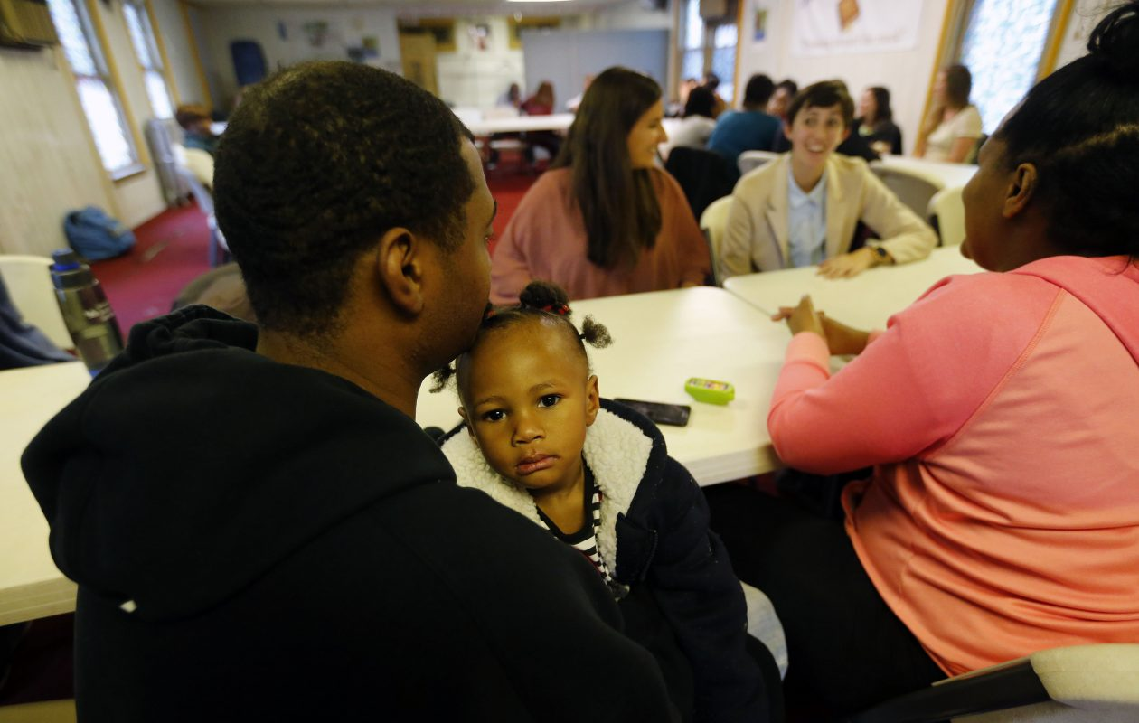 Michael McCarriel holds his daughter, Kamera, as his wife, Shakera, talks with University at Buffalo medical students Christine Toufexis, left, and Lauren Lucente at Hopewell Baptist Church on Fillmore Avenue. (Mark Mulville/Buffalo News)