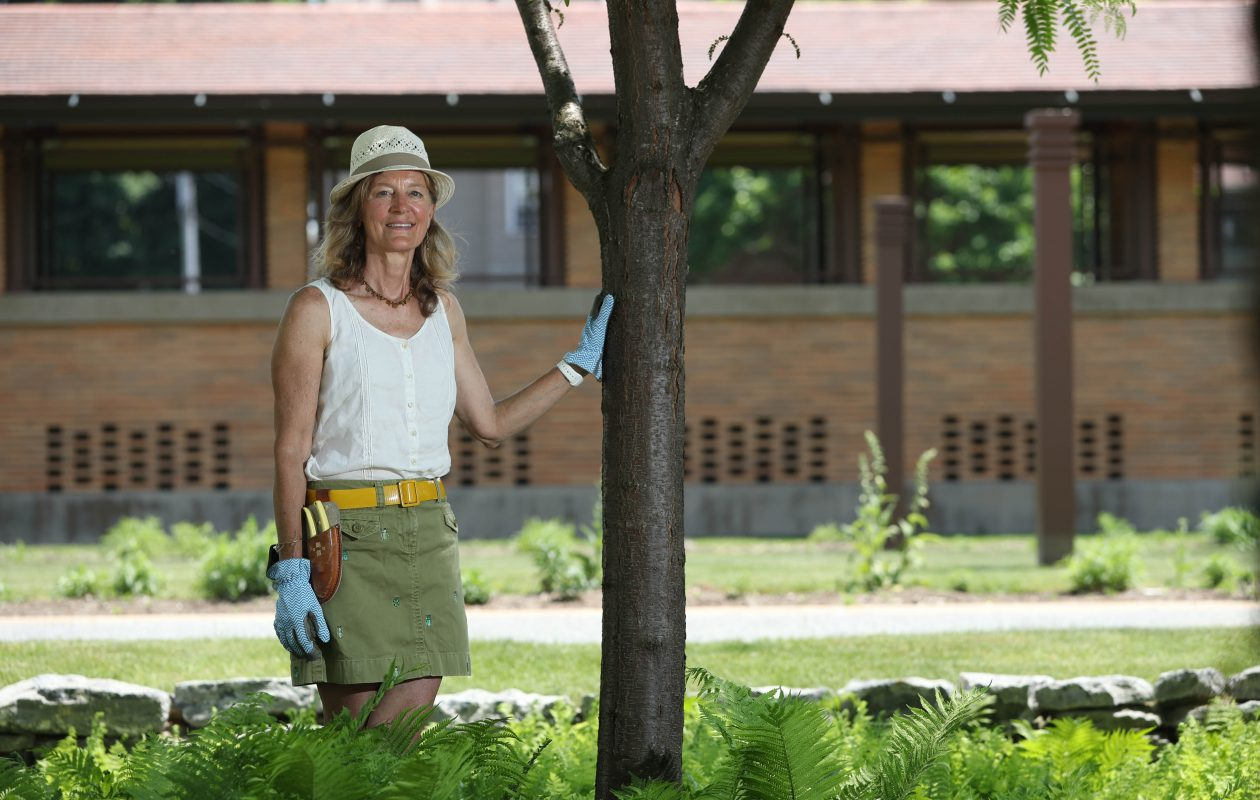 Horticulturist Nellie Gardner, on the grounds of Frank Lloyd Wright's Darwin Martin House Complex on Jewett Parkway, has a fashion style all her own. In photographs, Martin often had his hand on a tree, she said, which is why she chose this pose for a  photo. (Sharon Cantillon/Buffalo News)