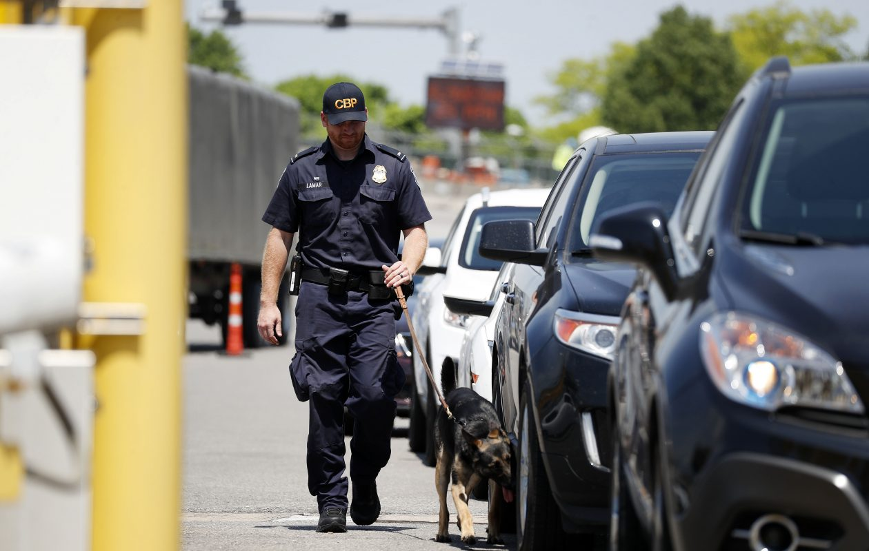 Don Lamar, a U.S. Customs and Border Protection canine enforcement officer, and his drug-sniffing partner Cloe inspect vehicles at the Peace Bridge. Such inspections may increase when marijuana legalization takes effect in Ontario in a few weeks. (Mark Mulville/Buffalo News)