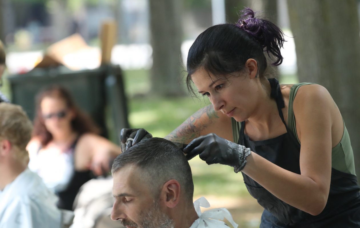 Charlene Minx cuts Louis Kaetzel's hair for free at Fireman's Park in Buffalo on Sunday, June 17, 2018.  (James P. McCoy/Buffalo News)