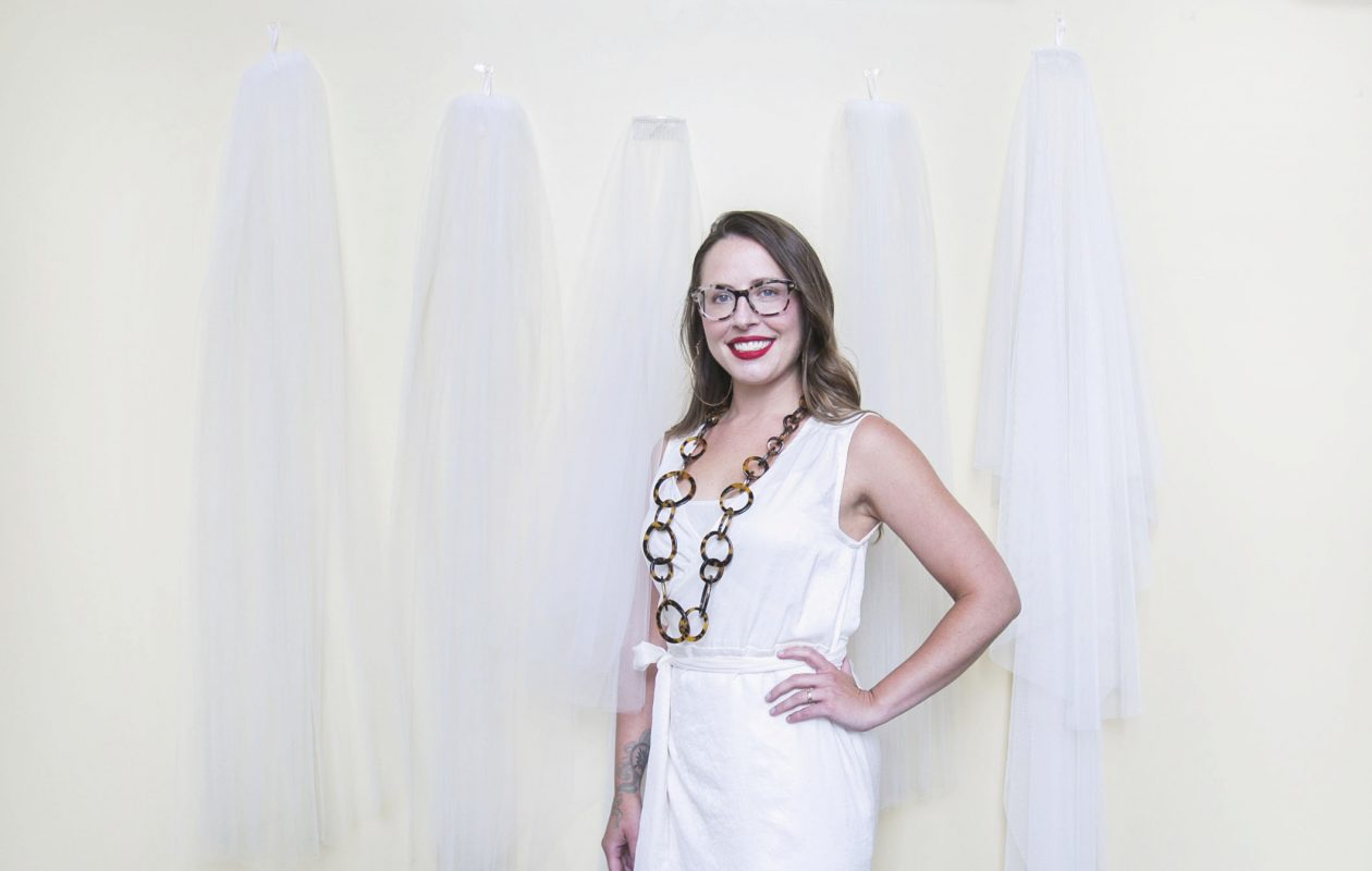 Ali Eagen, a custom wedding dress designer who owns made by anatomy, wears a few of her favorite things in her studio at Hotel at the Lafayette. On the wall behind her are fabric samples for veils.  (Shuran Huang/Buffalo News)