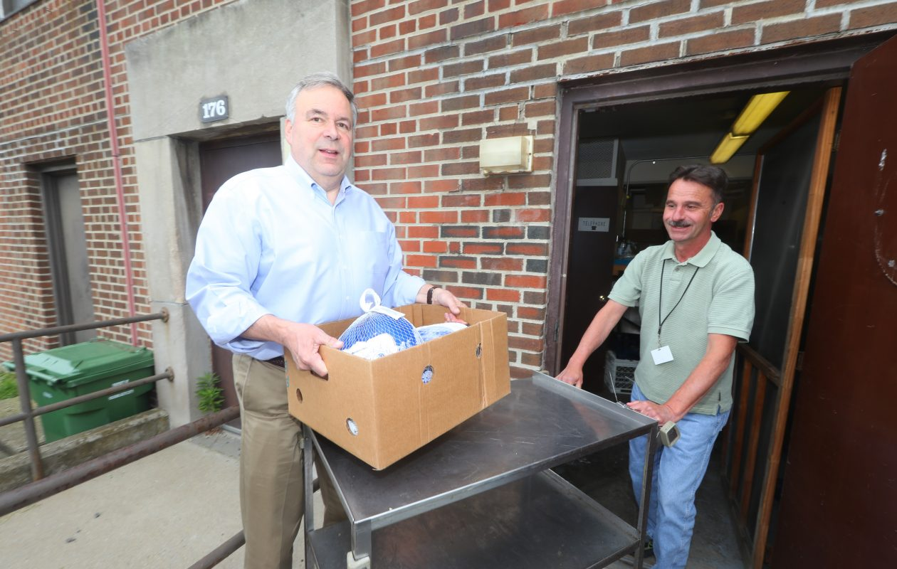 David Rogers, left, CEO of Life Storage (formerly Sovran Self Storage), delivers food to Bill Larsen, outreach coordinator at Fulton Street-St. Brigid Food Pantry, as part of his effort to help Catholic Charities. (John Hickey/Buffalo News)