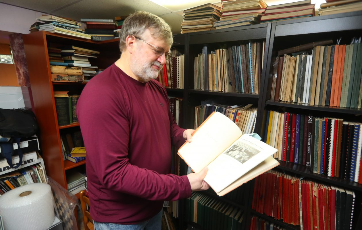William Greco, a former Roswell researcher, looks at a photo of Robert E. Schmidt as a freshman in a 1930 yearbook from Fosdick Masten High School in Buffalo. Schmidt went on to become the famed 'Buffalo Bob' Smith. Greco has almost 700 yearbooks, most from Buffalo, in his collection. (John Hickey/Buffalo News)