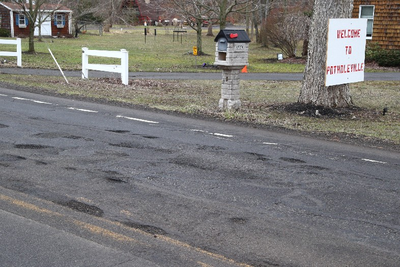 'Welcome to Potholeville' reads a sign along Lakeview Road in Hamburg. Road conditions remain terrible around Erie County, three months after that picture was taken in late March. (John Hickey/Buffalo News)