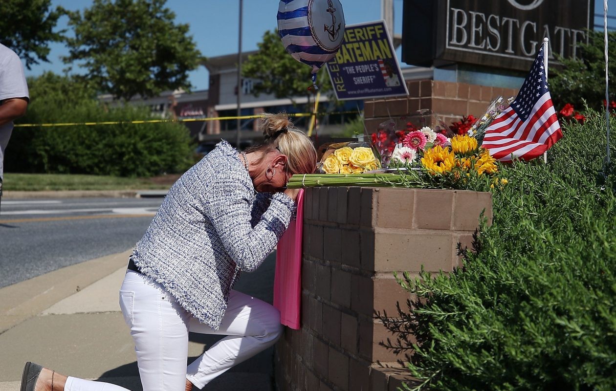 ANNAPOLIS, Md. - Lynee Griffin pays her respects at a makeshift memorial near the Capital Gazette where five people were shot and killed by a gunman on Thursday. Griffin was a journalism student under John McNamara, one of the journalists who died at the paper.   (Photo by Mark Wilson/Getty Images)