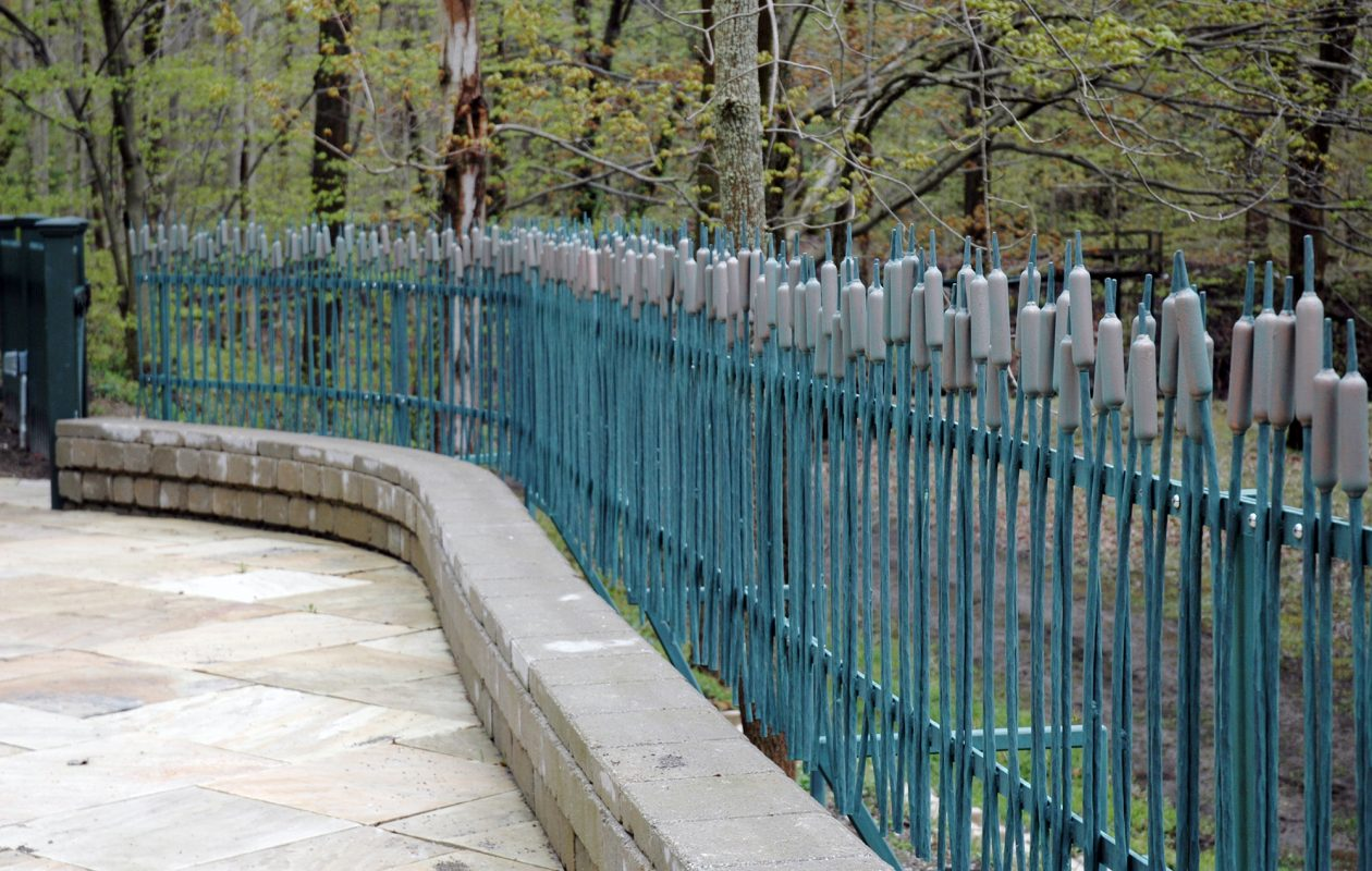 Blacksmith Andy Chambers of Arc Iron Creations forged this steel fence to resemble cattails. Located in a Buffalo suburb, the fence is 100 feet long with a verdigris finish over bronze paint to give it an aged copper look.